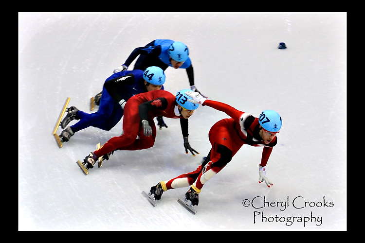 American skater J.R. Celski in fourth place closes in on Canada's skaters Olivier Jean in first in the final laps of the men's speed skating relay race. in the 2010 Vancouver games.