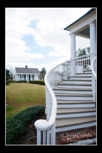 The graceful curved stairway leads to the upper gallery porch of the plantation's big house.
