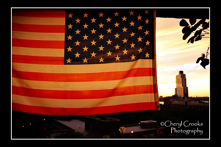 Old Glory hung from the balcony faded by the sunset and offering a glimpse of the high rises behind.