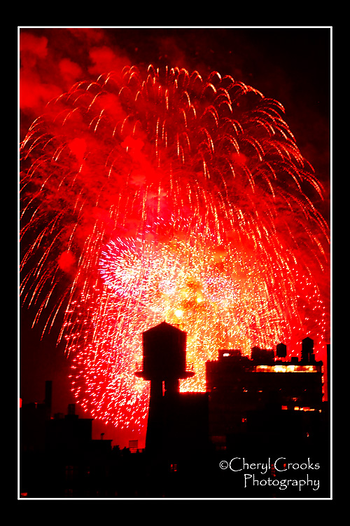 The exploding sprays of revolutionary red fireworks silhouetted the water tower atop one of the nearby buildings during the Fourth of July spectacular.