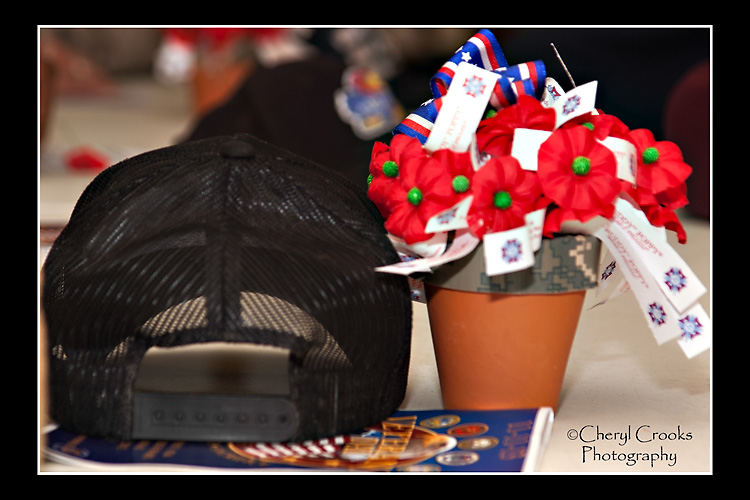 My Dad's favorite cap, with a logo identifying him as a World War II veteran, rests quietly beside the pot of poppies at the 2013 Veterans Day ceremony.