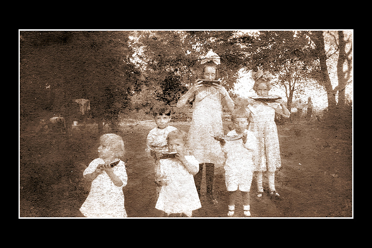 This snapshot is taken from my Dad's family albums and shows him and some of his siblings enjoying a slice of watermelon. If you look carefully, you can see two men in the background the identities of whom I'm uncertain.
