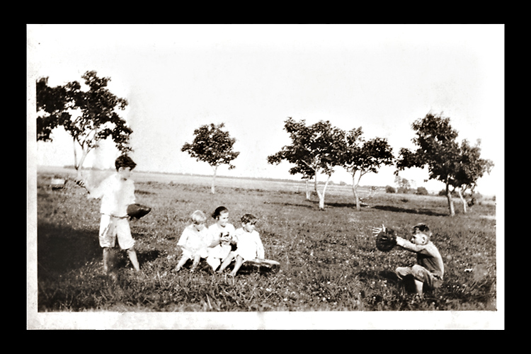 The great American pasttime of baseball being played by my uncles as children on their family farm. An unknown photographer captured my uncle Buck's wind-up just as he was about to toss the ball to his younger brother, James.