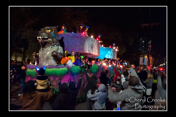 Parade goers raise their arms in hopes of catching  a throw tossed from the masked riders on one of the floats during Cleopatra's parade.