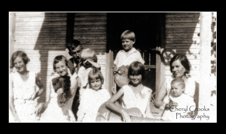 My mother, holding guitar, with her parents and sisters and brothers pose for photo on their porch.