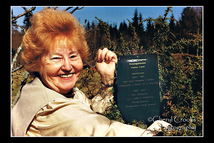 My aunt holds back the bush to reveal the plaque commemorating her family at the Swedish farmstead.
