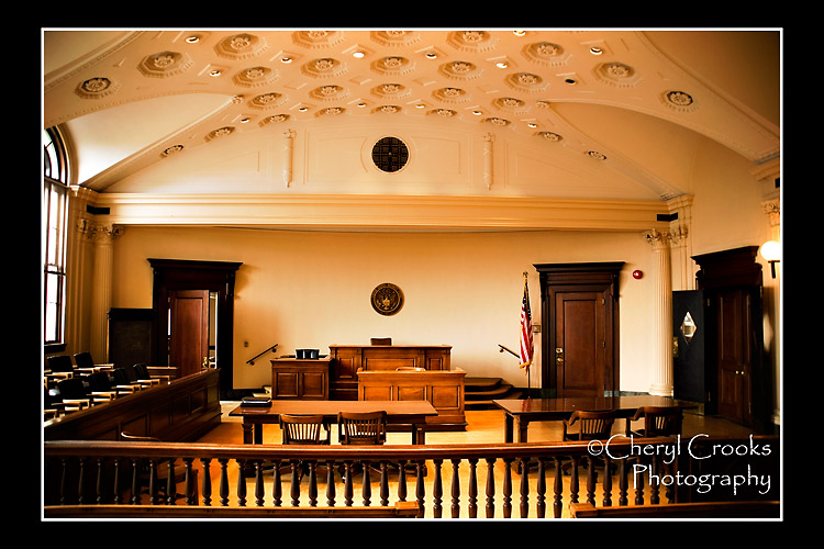 The audience is separated from the court floor by a mahogany railing that spans the width of the courtroom.