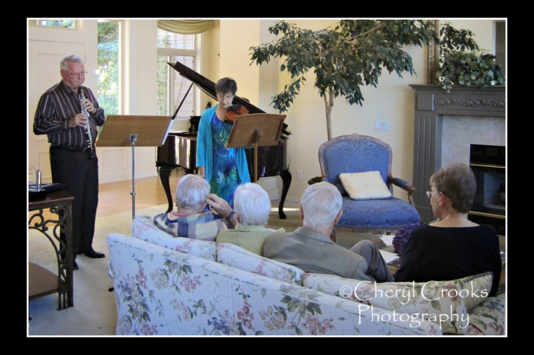 Mary Kary and Joe Robinson play for guests during a farewell gathering given at a private home to honor their retirement from the Belingham Music Festival.