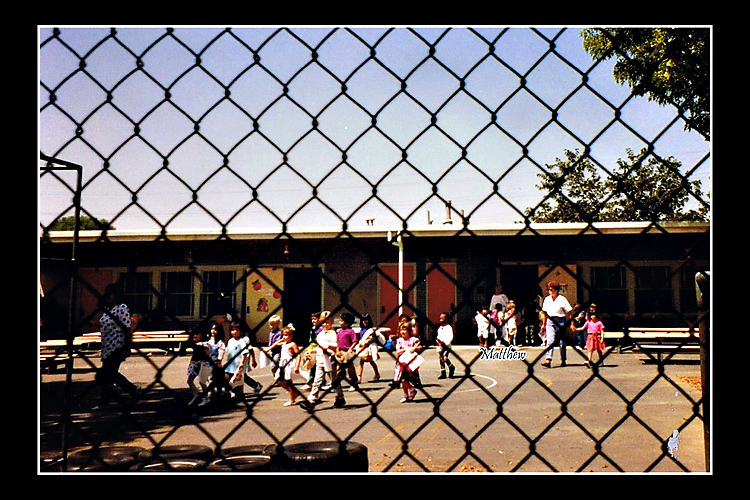 Kindergartners, my son among them, parade out the classroom and across the playground at the end of their first day.