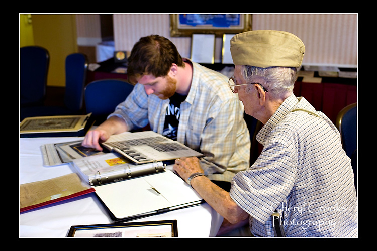 My Dad share a story from his World War II military service with my son as they look through photos on display at one of my Dad's army reunions.