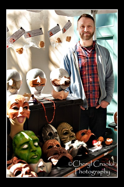 Portland, Ore.-based mask maker Tony Fuemmeler stands beside some of his creations on display at the Mardi Gras Mask Market.