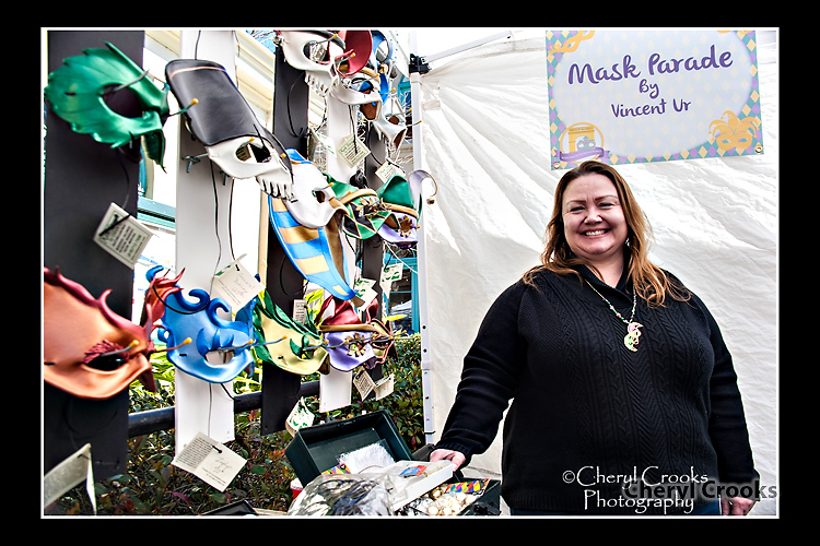 Veronica Ur stands alongside some of her husband, Vincent Ur's, masks available for purchase during the Mardi Gras Mask Market.