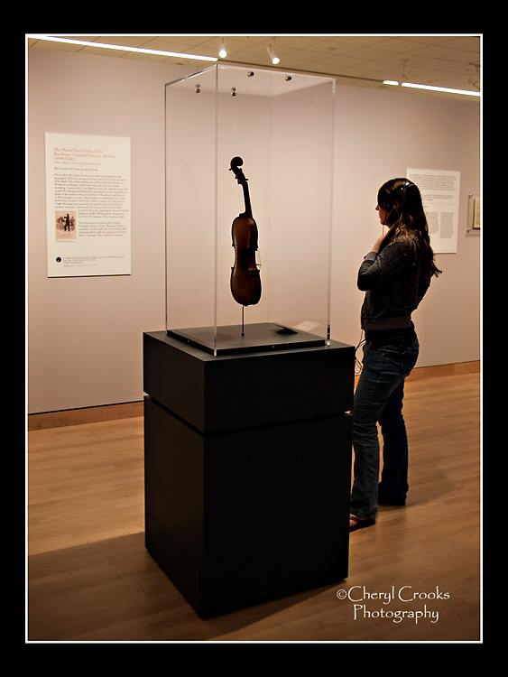 A visitor to the Stradivarius exhibit reads the description on the wall while listening to the music of the instrument on display.
