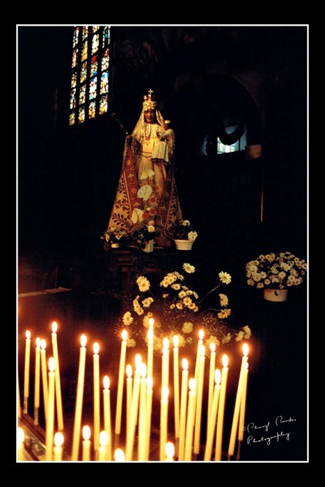 Candles lit by the faithful on Easter cast a glow on the statue of the Virgin Mary in the Church of Our Blessed Lady of the Sablon.