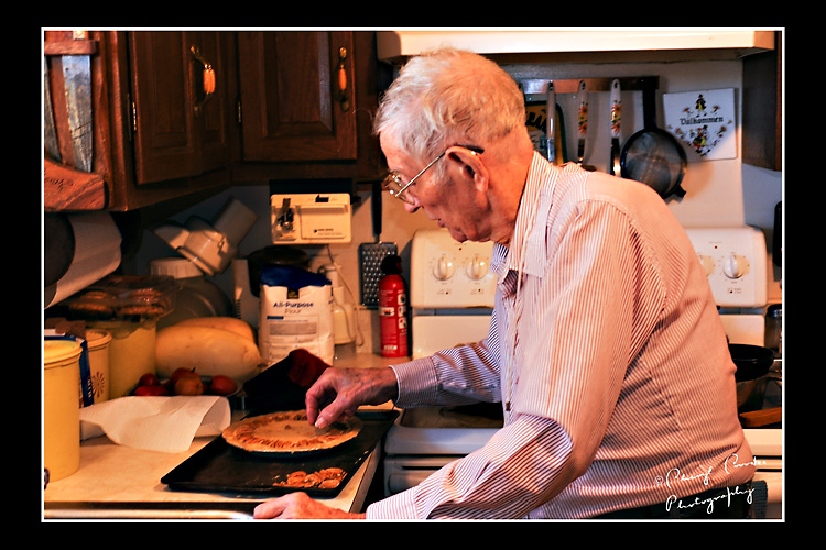 With a pile of pecans handy, my Dad begins the process of placing the nuts atop the uncooked pie.